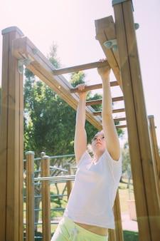 Tienerschoolmeisje die bij wildernisgymnastiek beklimmen