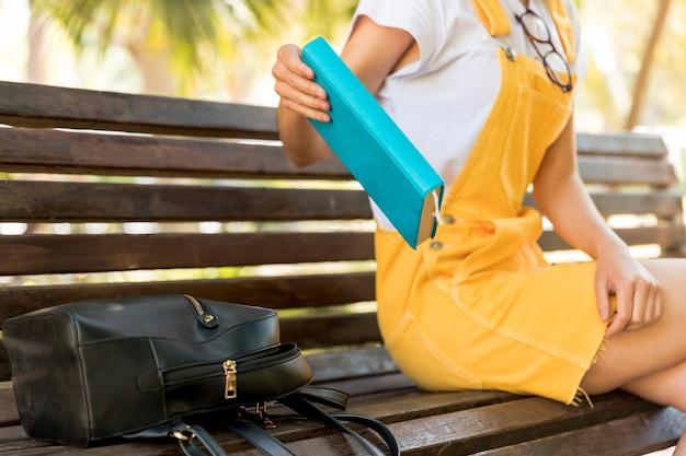 Tienerschoolmeisje die boek plaatsen aan bank
