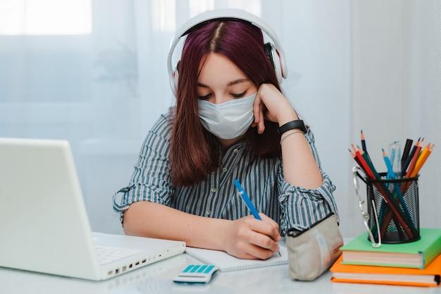 Tienerschoolmeisje die met medisch masker tegen virussen de bankstudent zitten die van de vloerwoonkamer huislaptop bestuderen die huiswerk doen