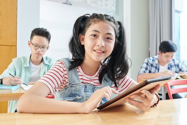 Tienerschoolmeisje die toepassing op tabletcomputer in klas gebruiken bij het werken aan taak