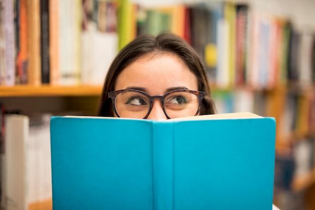 Tienerschoolmeisje die uit boek gluren
