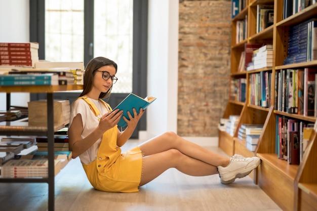 Tienerschoolmeisje met boek op vloer