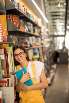 Tienerschoolmeisje met boeken dichtbij planken