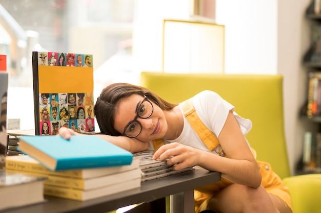 Tienerschoolmeisje rustend hoofd op lijst met boeken