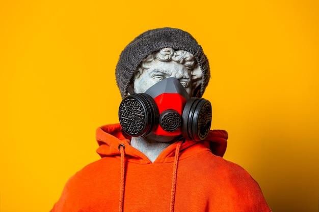 Tienersculptuur in oranje hoodie, gezichtsmasker en hoed op gele achtergrond