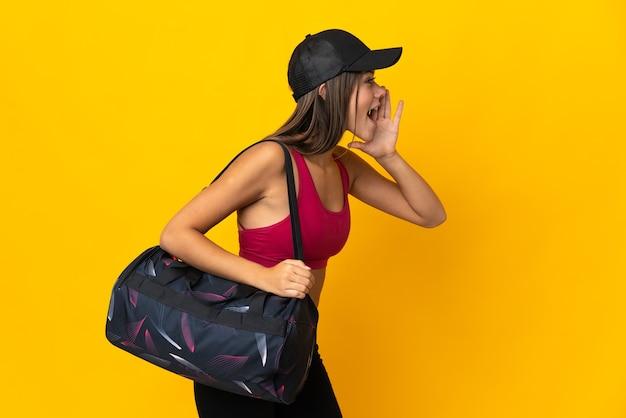 Tienersportmeisje die met sporttas met wijd open mond aan de kant schreeuwen