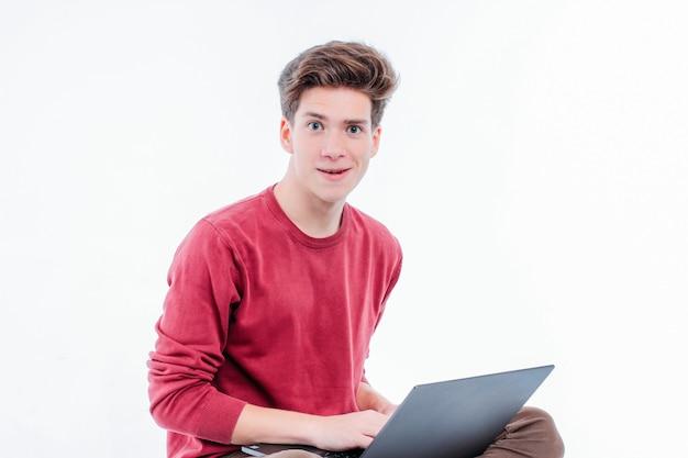Tienerstudent met grappig gezicht die bij laptop op witte rug werken