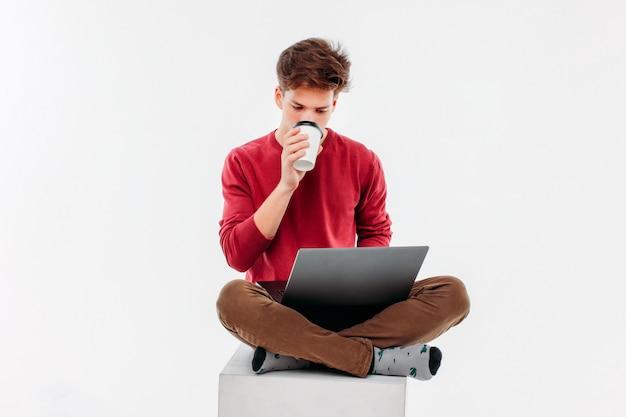 Tienerstudent met kop van koffie om bij laptop te werken