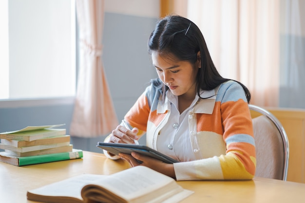 Tienerstudenten schrijven op het antwoordblad van het examenpapier in de klas