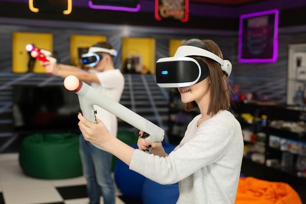 Tienervrienden, een jongen en een meisje, met een virtual reality-headset in een bril en handbewegingscontrollers in de gameclub.