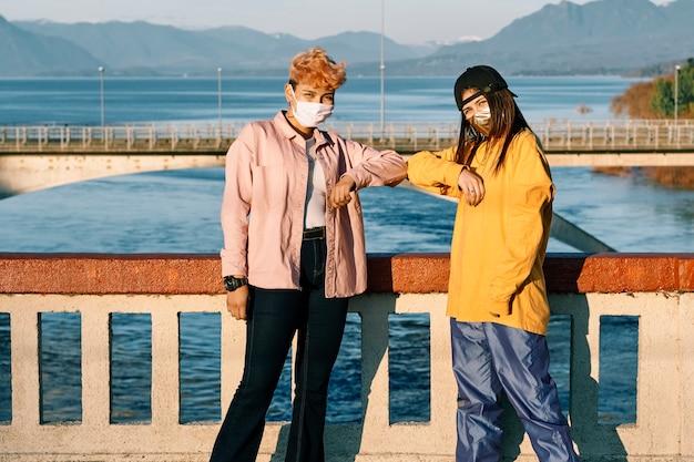 Tienervrienden met gezichtsmaskers die een nieuwe manier van verwelkomen tonen tijdens het covid-virus. concept van nieuwe normale en sociale afstand nemen