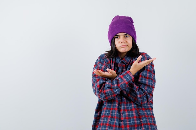 Tienervrouw die beide kanten in geruit overhemd en muts laat zien en besluiteloos kijkt