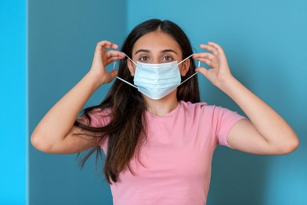 Tienervrouw die beschermend medisch masker opzet voor coronaviruspreventie tegen blauwe achtergrond