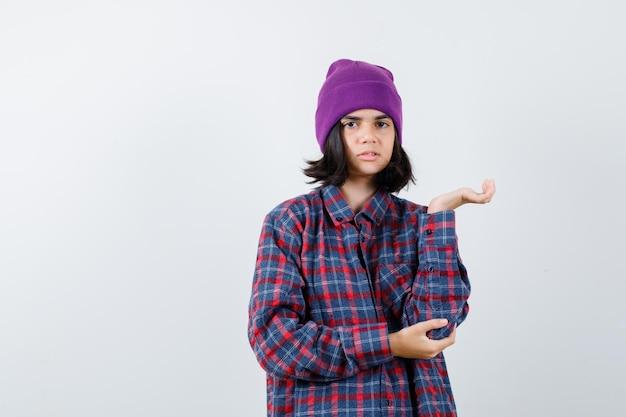 Tienervrouw die doet alsof ze iets in een geruit hemd ziet en er gefocust uitziet