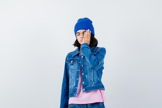 Tienervrouw die een deel van het gezicht bedekt met de hand in een roze t-shirt-jeansjasje en er serieus uitziet