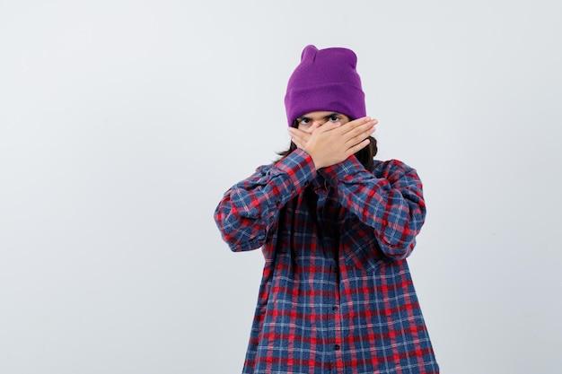 Tienervrouw die gezicht bedekt met handen in geruit overhemd en muts en er gefocust uitziet