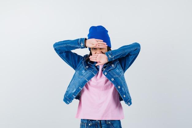 Tienervrouw die gezicht bedekt met handen in roze t-shirt die zich schamen