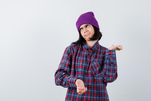 Tienervrouw die haar handpalmen opzij spreidt in een geruit overhemd en een beanie die er ontevreden uitziet