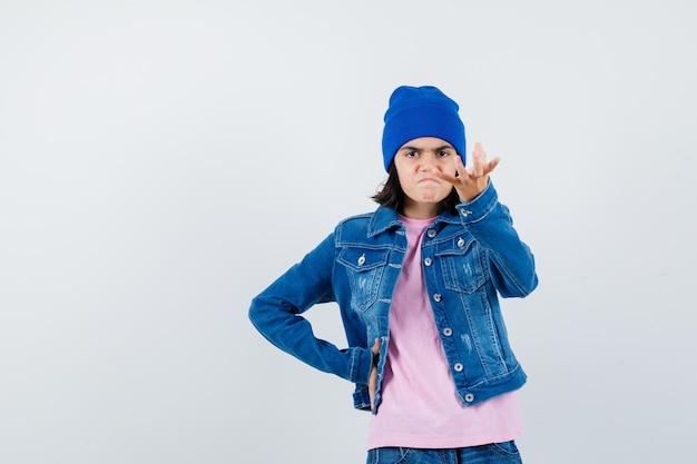 Tienervrouw die hand uitrekt terwijl ze iets denkbeeldigs vasthoudt en boos kijkt