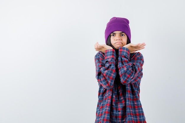 Tienervrouw die handen op een verbaasde manier opsteekt en er verward uitziet