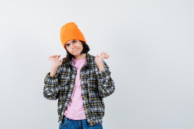 Tienervrouw die handen opheft in overgavegebaar in t-shirtjasje die ontevreden kijkt