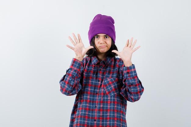 Tienervrouw die handen opsteekt in overgavegebaar beanie die er roekeloos uitziet