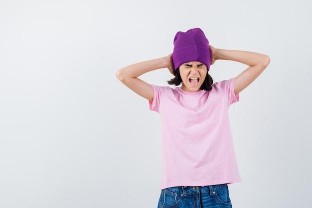 Tienervrouw die hoofd met handen omklemt terwijl ze schreeuwt in t-shirt en muts die angstig kijkt