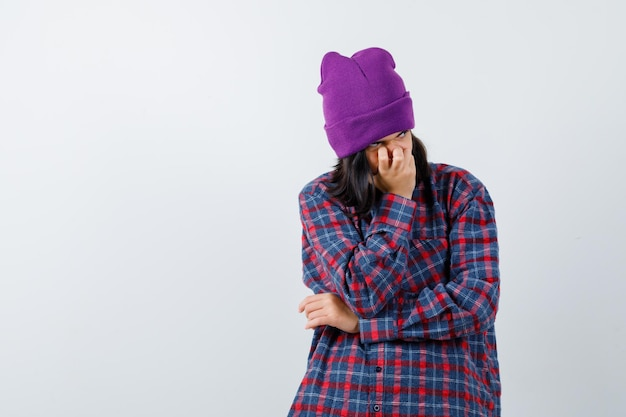 Tienervrouw die kin op handbeanie steunt die verbaasd kijkt