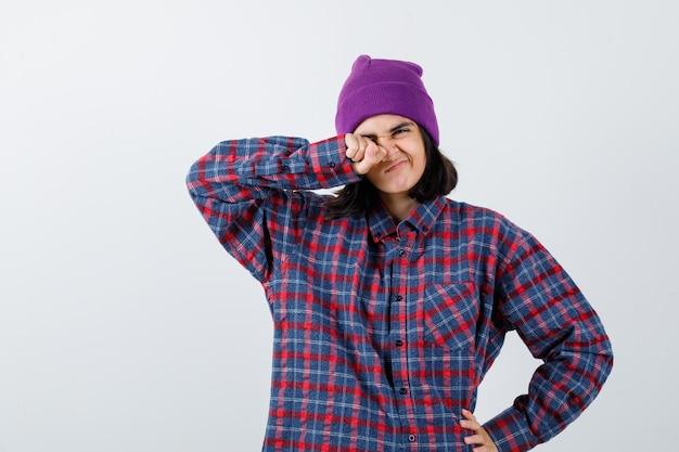 Tienervrouw die met vuist in oog wrijft en hand op heup houdt in geruit overhemd