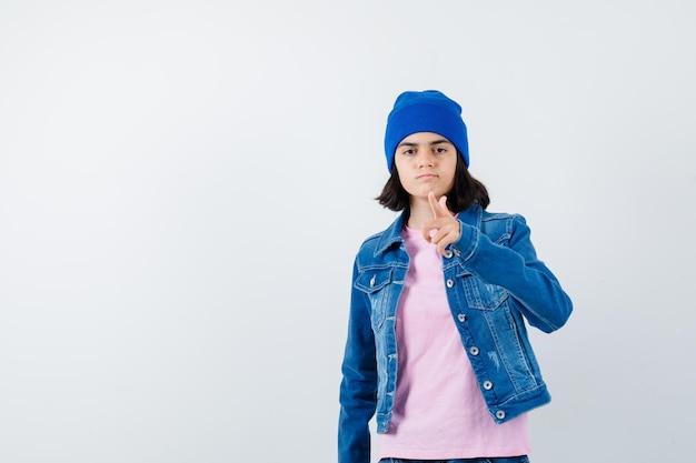 Tienervrouw die met wijsvinger wijst en er zelfverzekerd uitziet