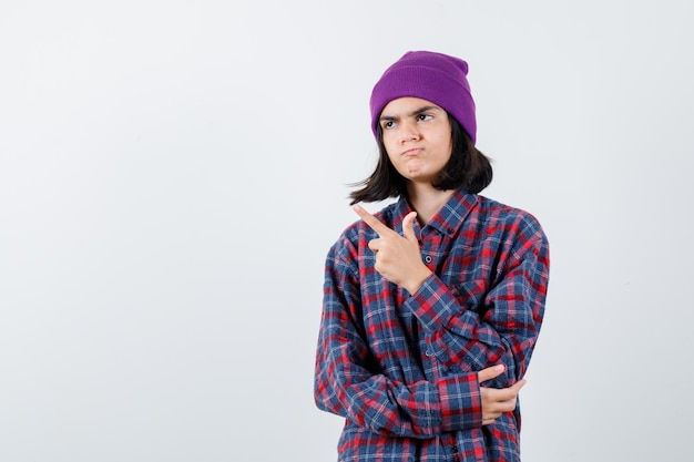 Tienervrouw die naar links wijst met wijsvinger die hand op elleboog houdt