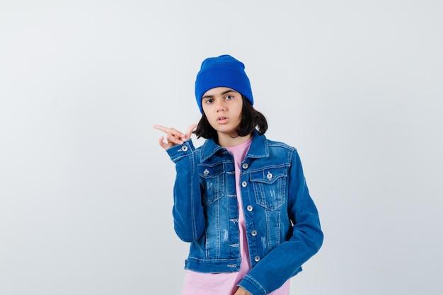 Tienervrouw die naar links wijst met wijsvinger in roze t-shirt spijkerjasje beanie die er serieus uitziet