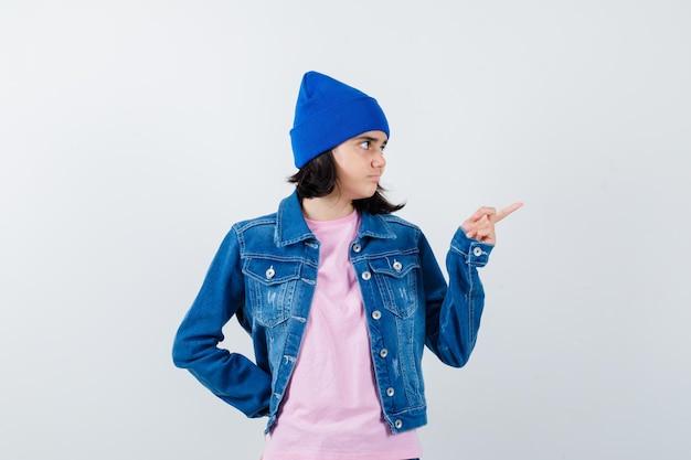 Tienervrouw die naar rechts wijst met wijsvinger die hand achter taille houdt
