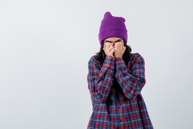 Tienervrouw die ogen bedekt met handen in geruit overhemd paarse muts die geïrriteerd kijkt