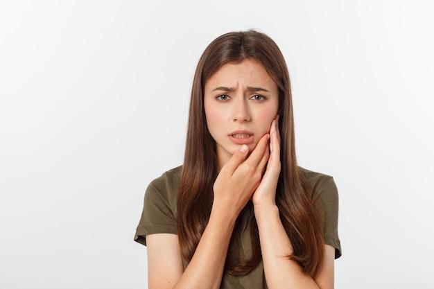 Tienervrouw die op haar gekneusde wang drukt met een pijnlijke uitdrukking alsof ze vreselijke tandpijn heeft