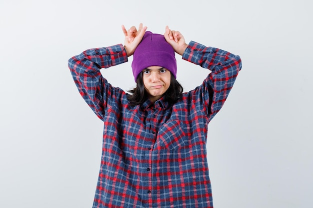 Tienervrouw die vingers boven het hoofd houdt als stierenhoorns in een muts die er ontevreden uitziet
