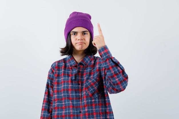 Tienervrouw die wijsvinger in eureka-gebaar opsteekt en er verstandig uitziet