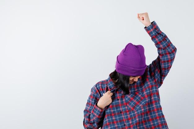 Tienervrouw die winnaargebaar in geruit overhemd en muts toont die geluk hebben