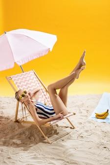 Tienervrouw het stellen in buitensporig badpak op de zomerachtergrond