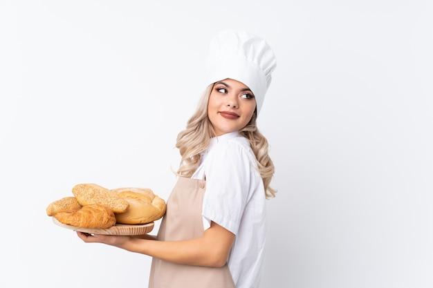Tienervrouw in eenvormige chef-kok. vrouwelijke bakker die een lijst met verscheidene broden over het geïsoleerde witte lachen houdt