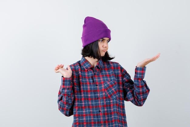 Tienervrouw in geruit overhemd en muts die doet alsof ze iets laat zien dat besluiteloos lijkt