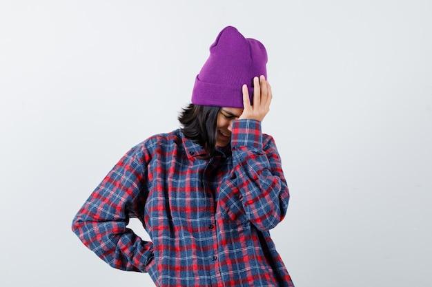 Tienervrouw in geruit overhemd en muts die geïrriteerd kijkt