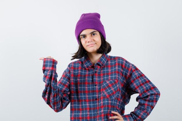 Tienervrouw in geruit overhemd en muts die palm opzij spreidt en er vrolijk uitziet