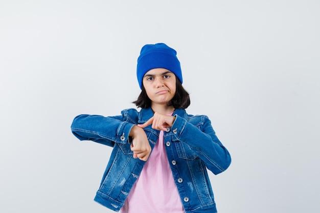 Tienervrouw in roze t-shirt die doet alsof ze met de wijsvinger wijst om er schattig uit te zien