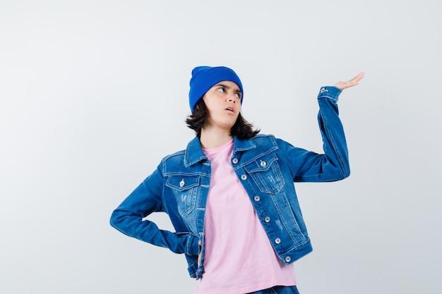 Tienervrouw in roze t-shirt en muts die hand op heup houdt en tot een kom gevormde hand uitrekt