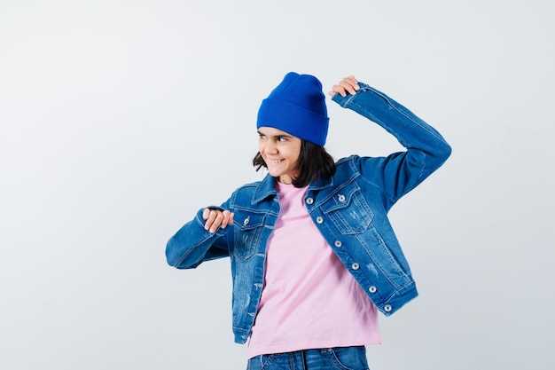 Tienervrouw in roze t-shirtjeansjasje en muts die winnaargebaar toont
