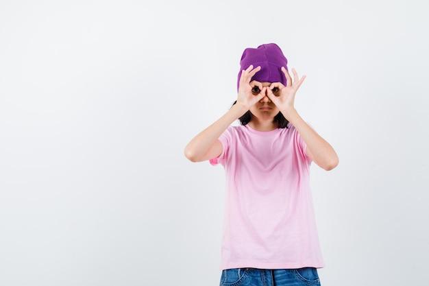 Tienervrouw in t-shirt en muts die een brilgebaar toont en er nieuwsgierig uitziet