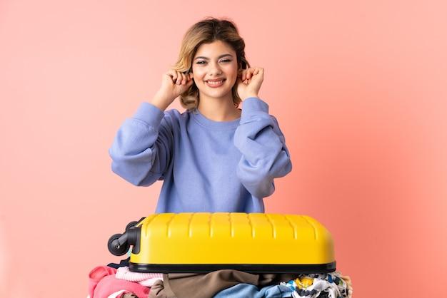 Tienervrouw met salade die op gefrustreerd roze en behandelende oren wordt geïsoleerd