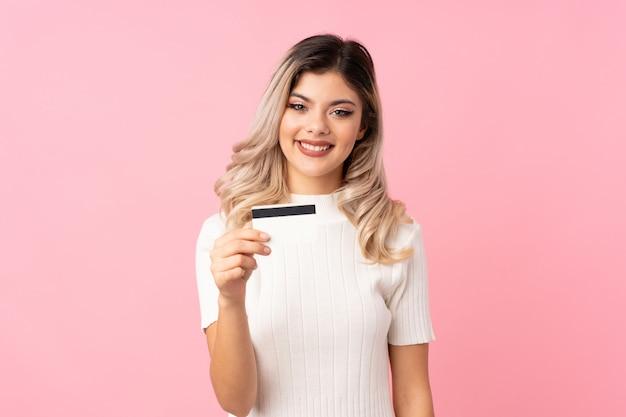 Tienervrouw over geïsoleerd roze die een creditcard houden