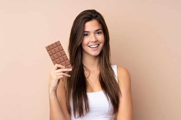 Tienervrouw over geïsoleerde muur die een chocoladetablet nemen en gelukkig